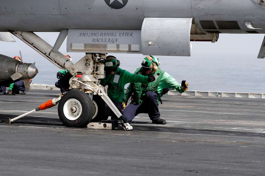 Sailors inspect an aircraft and a catapult shuttle before launching an F/A-18C Hornet from the Wildcats of Strike Fighter Squadron (VFA) 131 during flight operations aboard the Nimitz-class aircraft carrier USS Dwight D. Eisenhower (CVN 69).