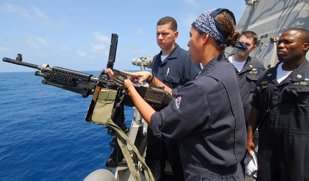 Fire Controlman 1st Class Ronila Ivory uses inert ammunition to demonstrate how to load an M240 machine gun during crew-served weapons familiarization training aboard the littoral combat ship USS Freedom (LCS 1).