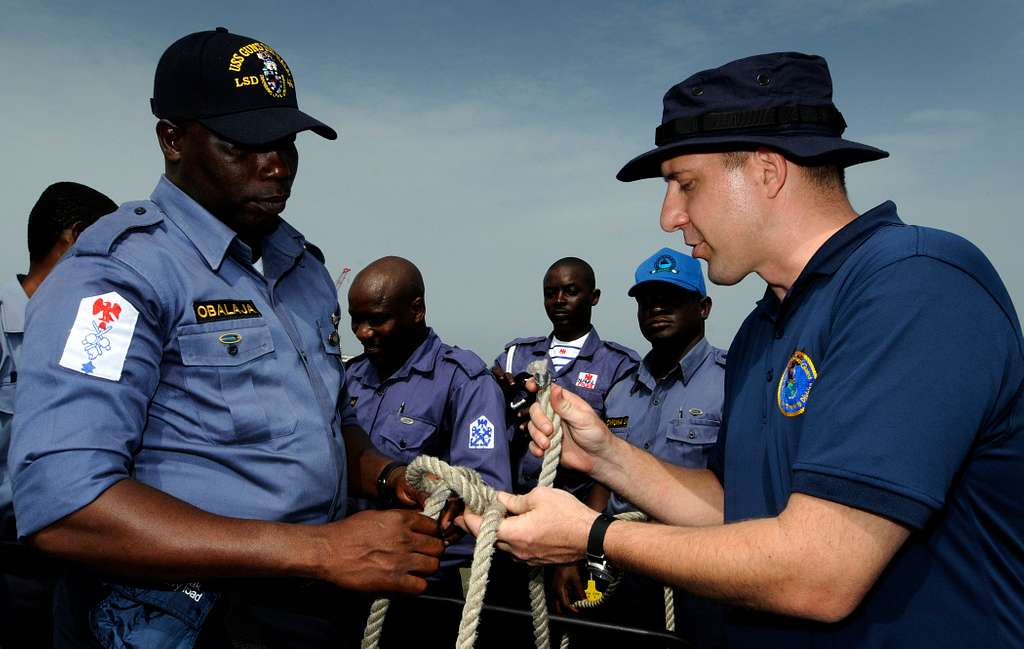 Coast Guard Chief Warrant Officer 3 Earl Schlemmer shows Nigerian navy Petty Officer Ademola Obalaja proper knot-tying techniques during a basic small boat operation workshop.