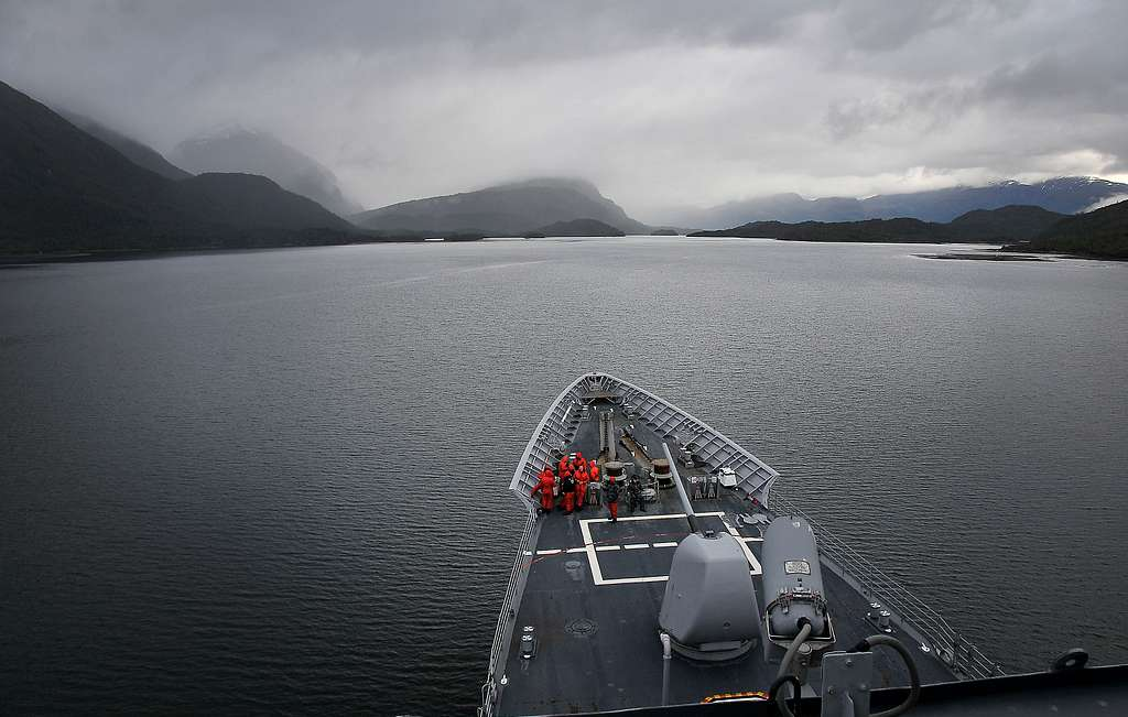 Sailors aboard the guided-missile cruiser USS Bunker Hill (CG 52) stand watch as the ship passes by mountains in southern Chile.