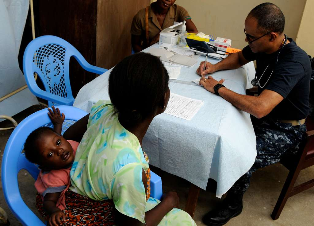 Cmdr. Antonio Rodriquez, from San Juan, Puerto Rico, performs a medical checkup on a Ghanaian woman and her child during a medical outreach program.