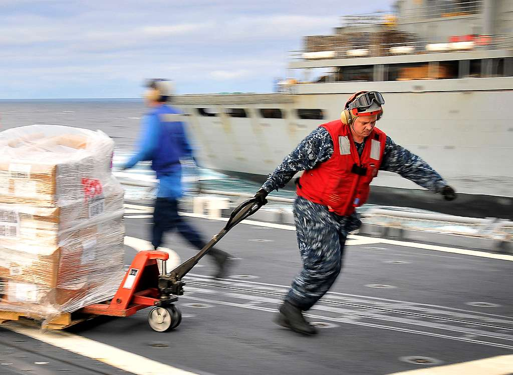 Ship's Serviceman 2nd Class John Duran pulls a palette of supplies aboard the guided-missile cruiser USS Bunker Hill (CG 52)