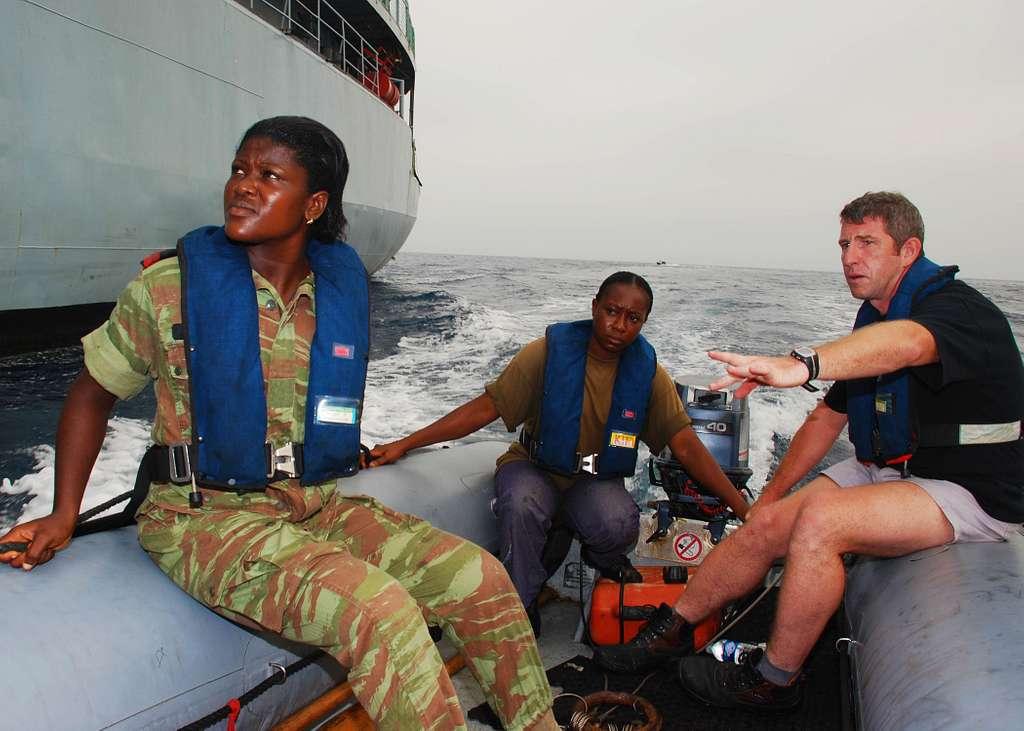 Belgian navy Cpl. Eddy Destaelen teaches Benin navy Quartermasters Seaman Chimene Djimahloue and Seaman Ahyi Ariane how to navigate a zodiac boat.