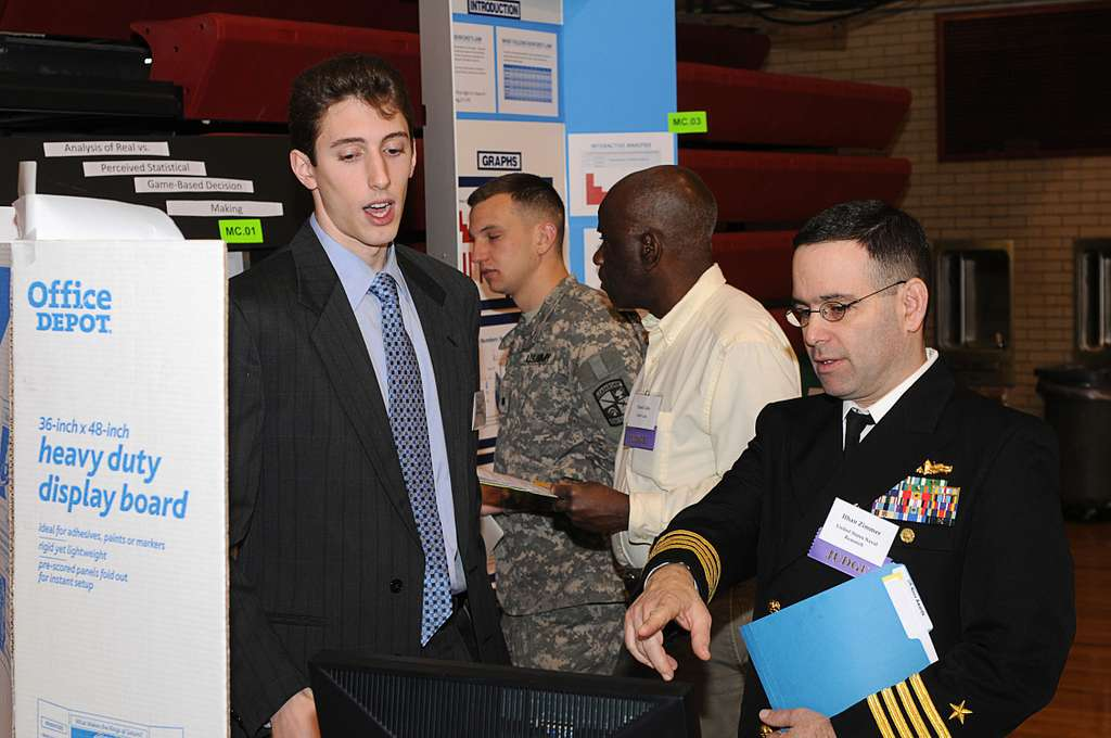 Capt. Ithan Zimmer, the Naval Science Fair coordinator for the Office of Naval Research, points to a contestant's computer monitor as he inquires about the student's project.