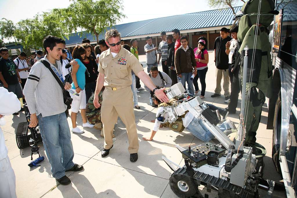 Chief Explosive Ordnance Disposal Technician Sean O'Leary shows a student at Carl Hayden High School a remote-controlled robot.
