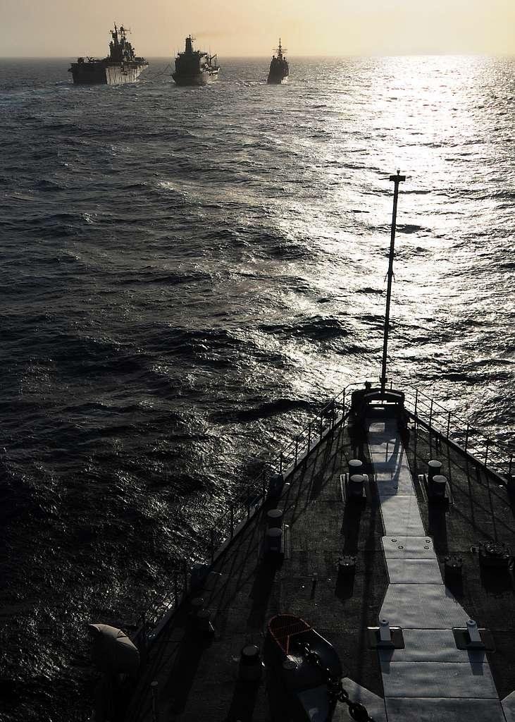 The amphibious assault ship USS Peleliu (LHA 5) and the amphibious transport dock ship USS Dubuque (LPD 8) receive fuel from the Military Sealift Command fleet replenishment oiler USNS Henry J. Kaiser (T-AO 187) during a replenishment at sea.