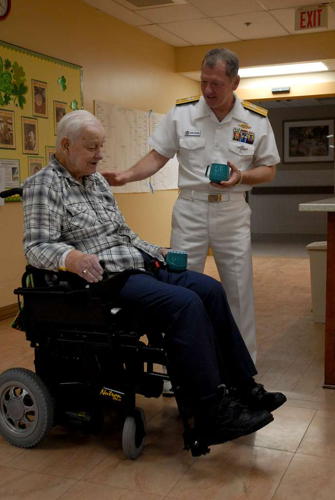 Rear Adm. Barry Bruner, commander of Submarine Group (COMSUBGRU) 10, talks to a Pearl Harbor survivor at the Veterans Affairs Hospital.