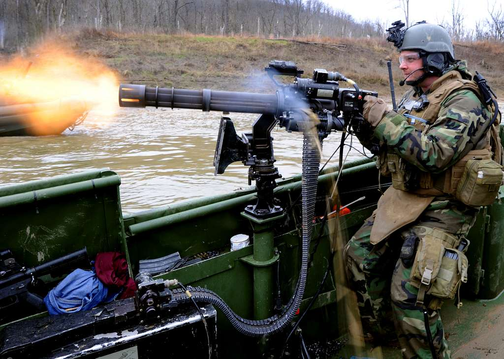 Gunner's Mate 3rd Class Geoffrey Martin fires a GAU-17A gun from the bow of a riverine assault boat during live fire battle drills at Fort Knox, Ky.