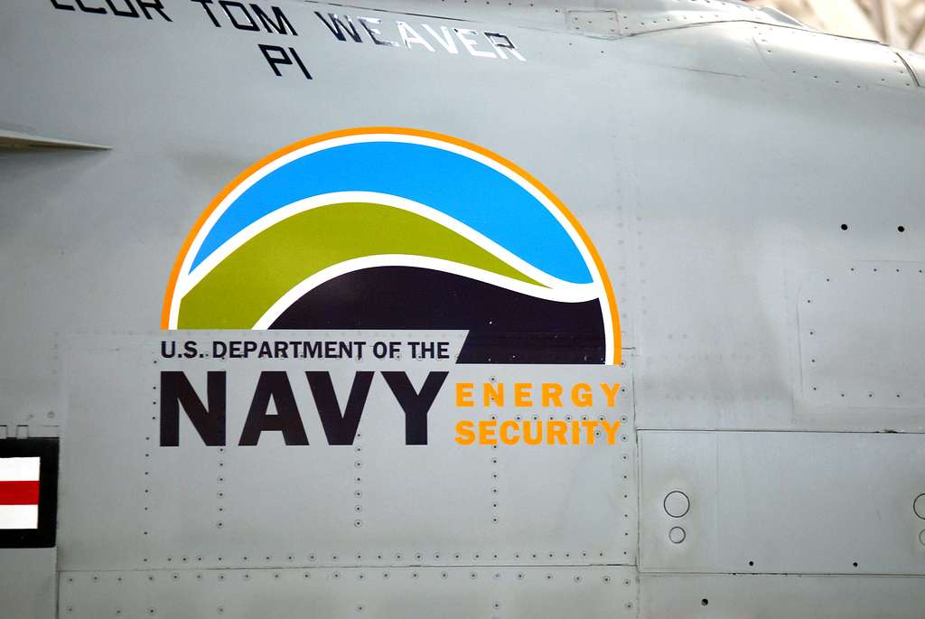 An F/A-18 Super Hornet from Air Test and Evaluation Squadron (VX) 23 with green markings and the U.S. Department of the Navy Energy Security logo.