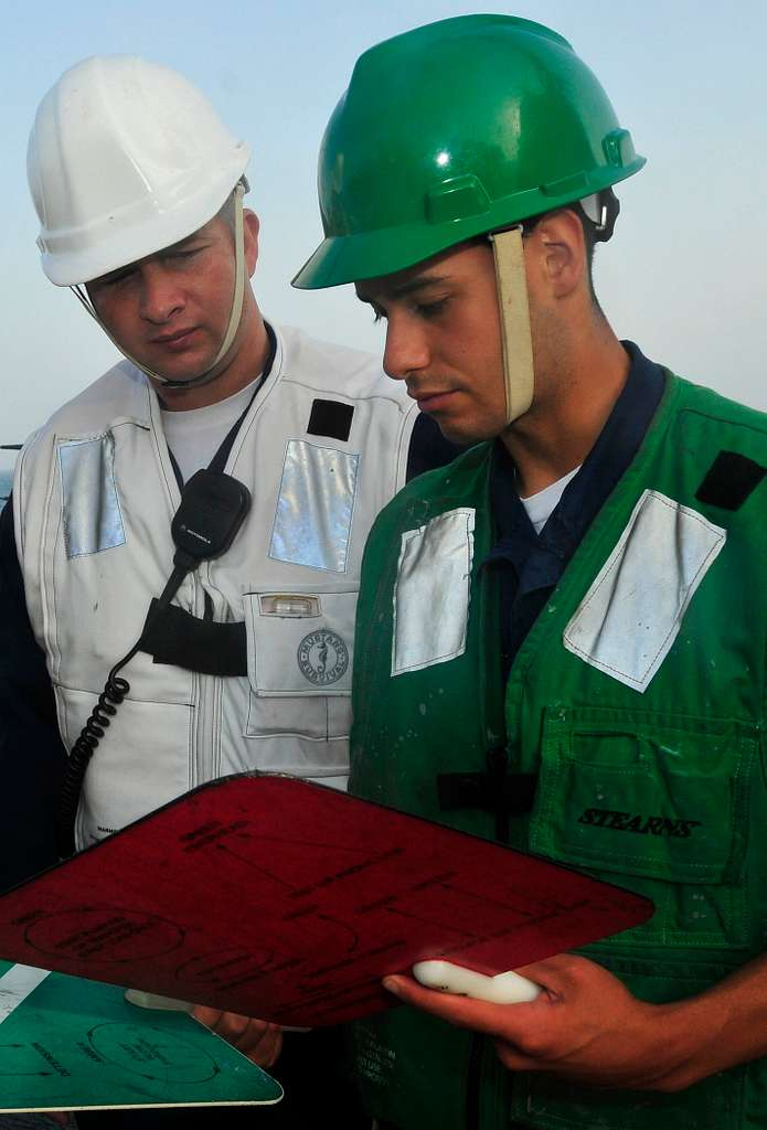 Chief Logistics Specialist William Griffis and Seaman Jonathan Perez discuss signal paddles.