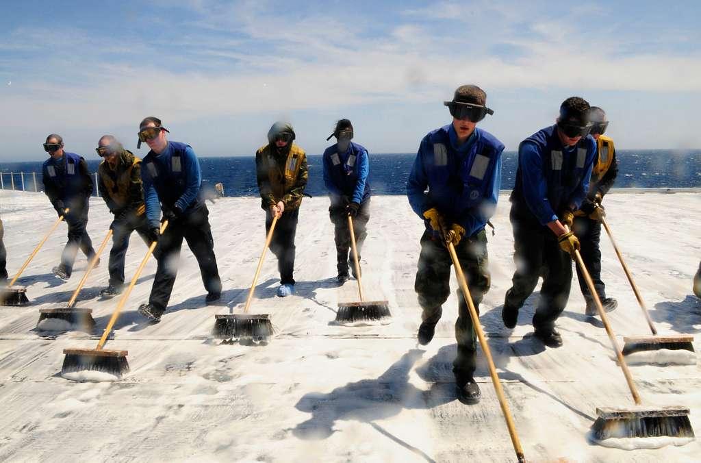 Sailors scrub the flight deck with aqueous film forming foam.