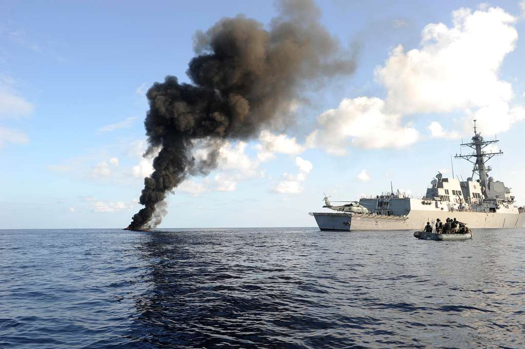 The Arleigh Burke-class guided missile destroyer USS Farragut (DDG 99) passes by the smoke from a suspected pirate skiff it had just disabled.