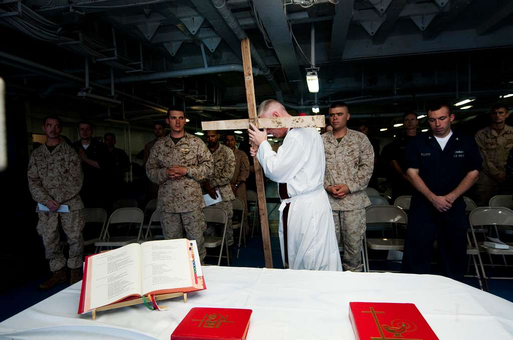 Lt. Jay Kersten holds up a wooden cross to symbolize the cross that Jesus was crucified on as Sailors celebrate Roman Catholic Mass.