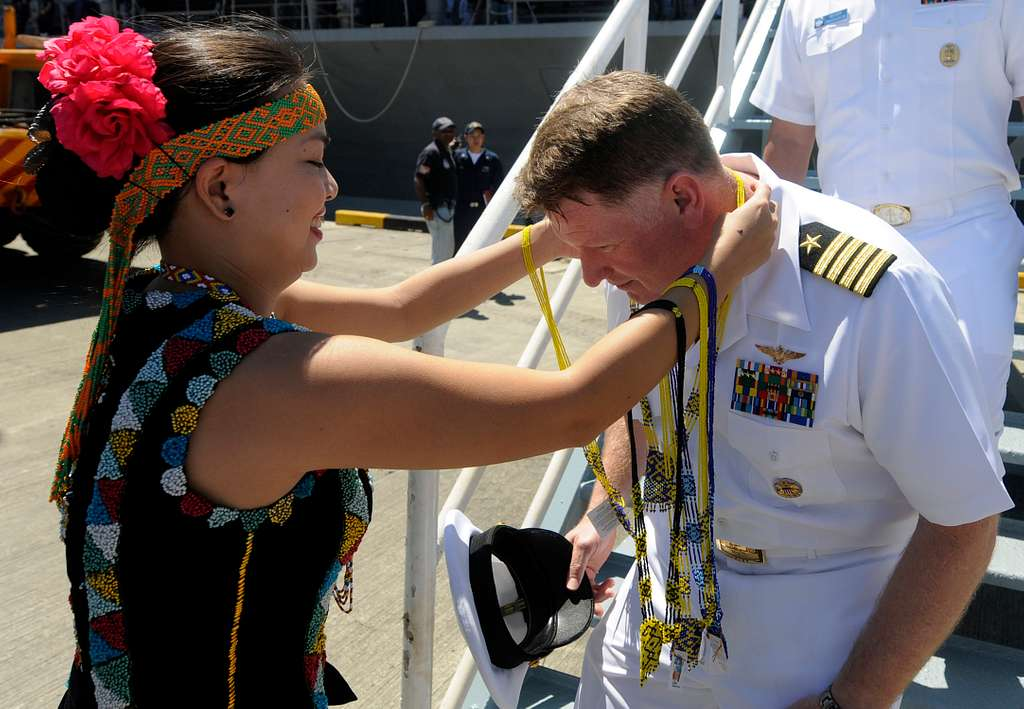 Capt. Rudy Lupton is welcomed with a litai necklace by Malay dancers.