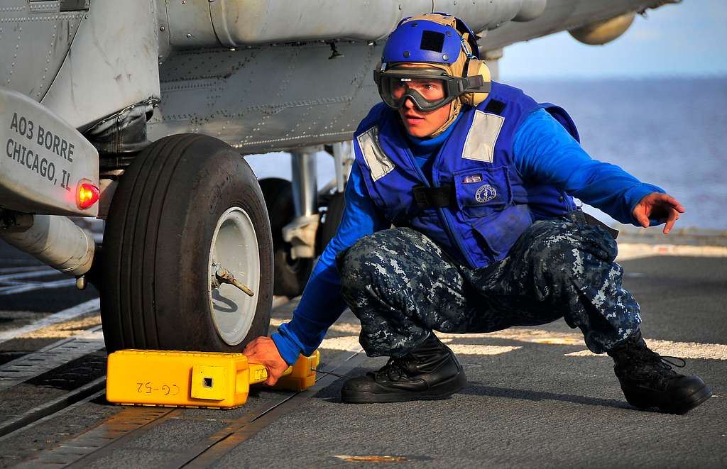 Boatswain's Mate Seaman Apprentice Anthony Orduna prepares to remove a chock from the landing gear of an SH-60F Sea Hawk helicopter.