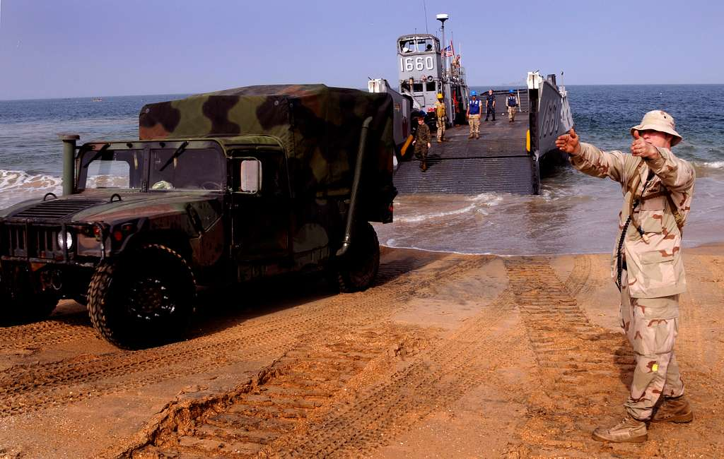 Information Systems Technician 1st Class Erik Lake directs a Humvee after it has disembarked from Landing Craft Utiity (LCU) 1660.