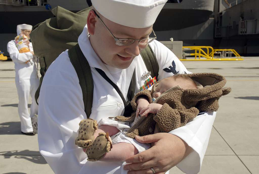 Machinist Mate 2nd Class Christopher Monroe, assigned to the Nimitz-class aircraft carrier USS Carl Vinson (CVN 70), holds his newborn son for the first time.