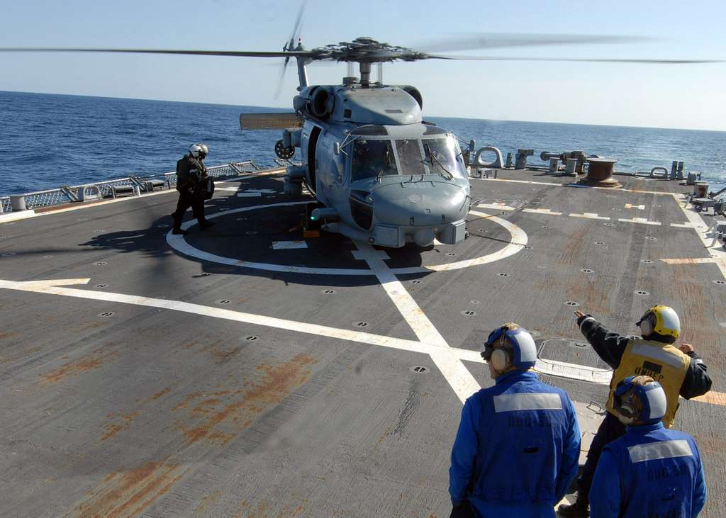 Boatswain's Mate 1st Class Chuyi Chang signals to the pilot of an SH-60B Sea Hawk helicopter, from Helicopter Anti-submarine Squadron (HS) 46, aboard the guided-missile destroyer USS Laboon (DDG 58) during exercise Joint Warrior 10-1.