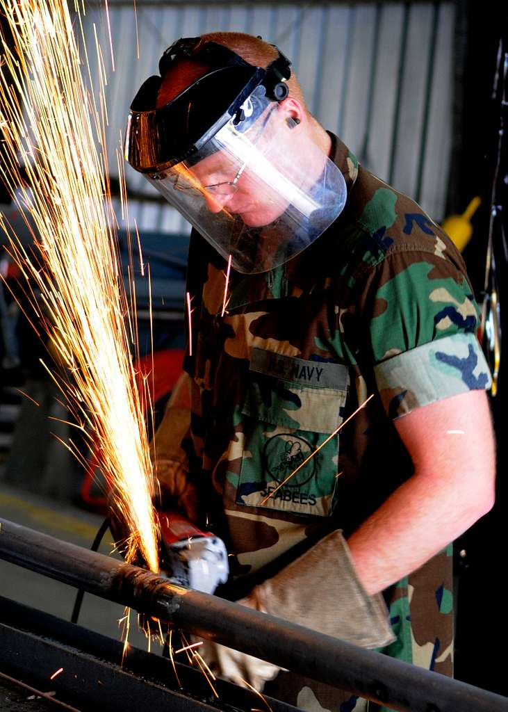 A Seabee grinds a pipe fitting to be used to fabricate a maintenance catwalk at a water treatment facility at Naval Station Rota, Spain.