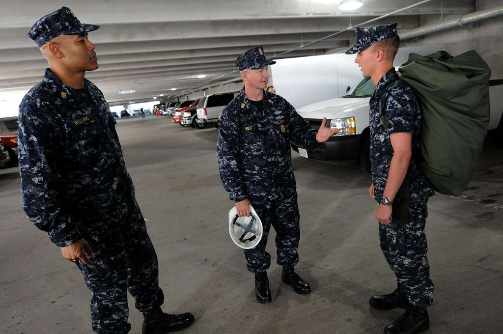 Master Chief Petty Officer of the Navy (MCPON) Rick West and Force Master Chief James Williams talk with Information Systems Technician Seaman Jacob Blizzard at Camp Allen.