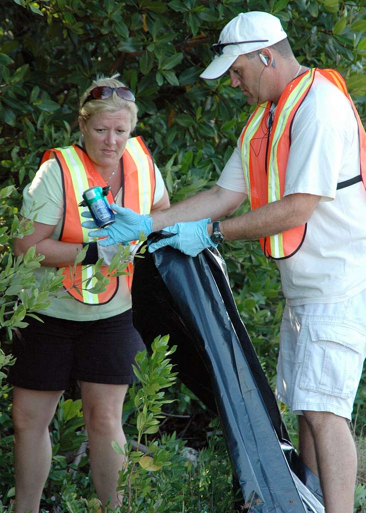 Naval Air Station Key West Command Master Chief Dan Messenger and his wife collect trash at Sigsbee Park Annex.