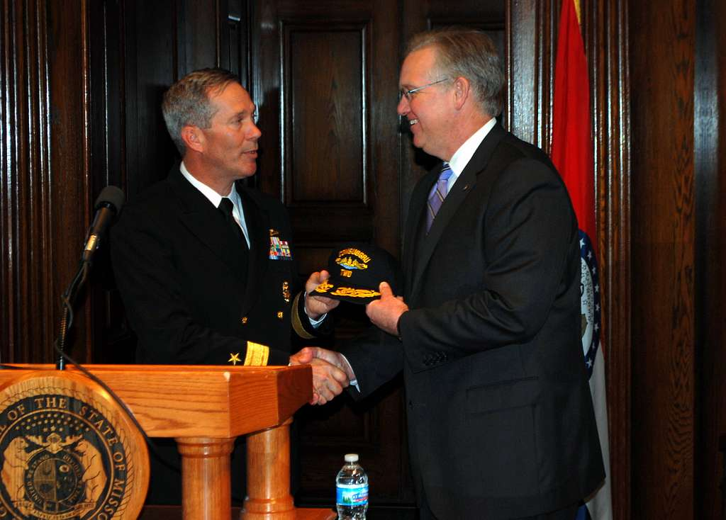 Rear Adm. Michael McLaughlin presents a group ball cap to Missouri Gov. Jay Nixon during a news conference.