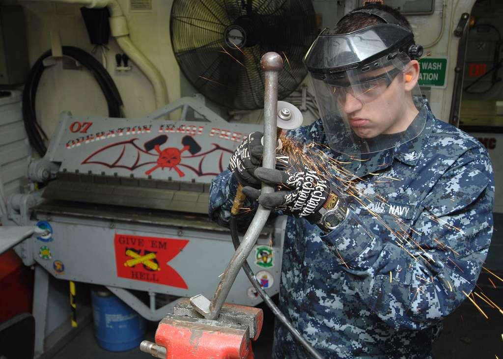 Aviation Structural Mechanic 3rd Class Jonathon Beck works on a door handle aboard the Nimitz-class aircraft carrier USS Harry S. Truman (CVN 75).