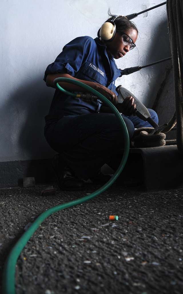 Seaman Erika Pattonhatchel uses a needle gun to chip away rust and paint on a mooring line cleat aboard the aircraft carrier USS Harry S. Truman (CVN 75).