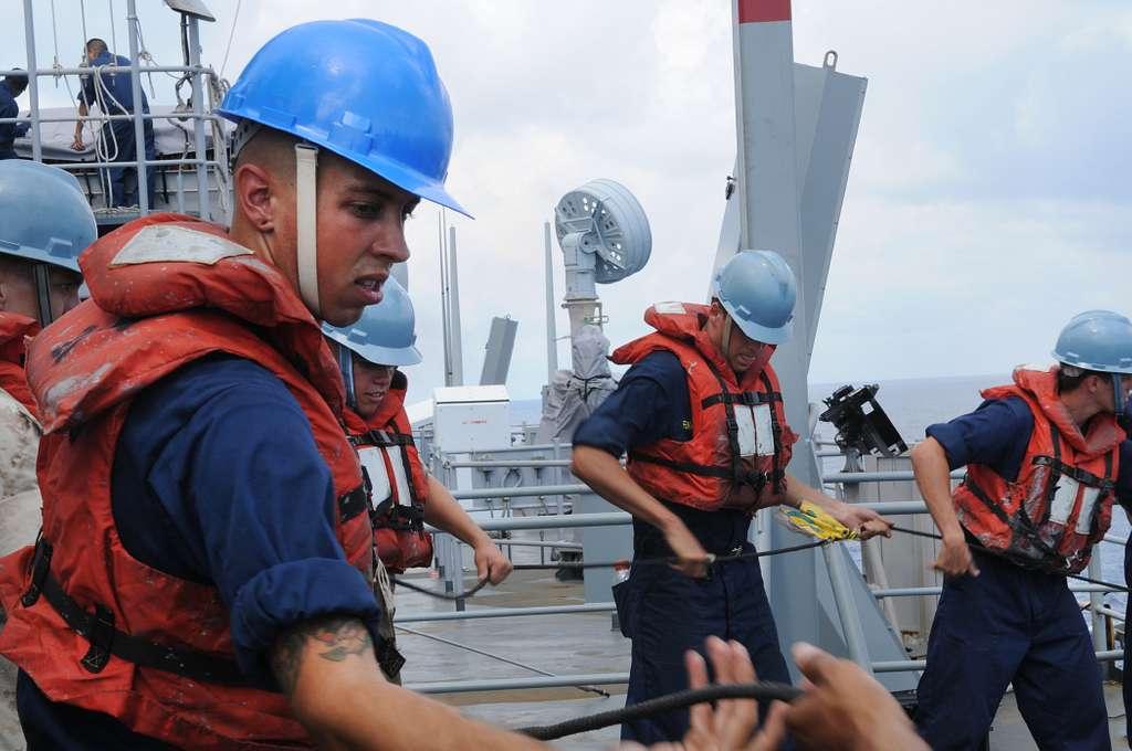 Sailors handle lines aboard USS Carter Hall