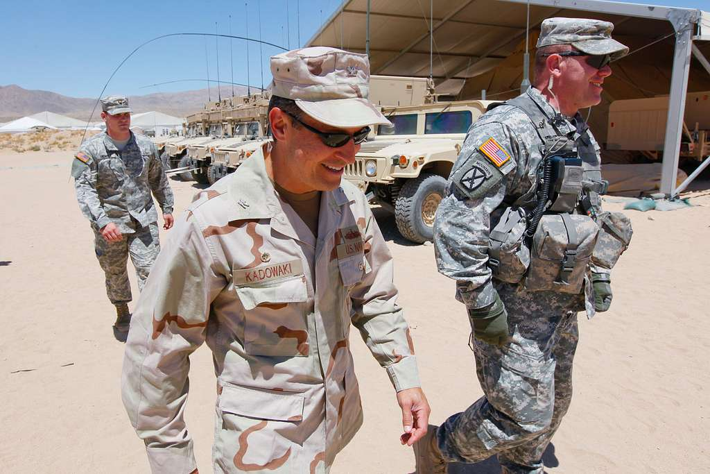 Capt. Jay Kadowaki walks with Maj. Brian Murphy, the brigade command intelligence trainer, during a visit to inspect the counter-improvised explosive device research.