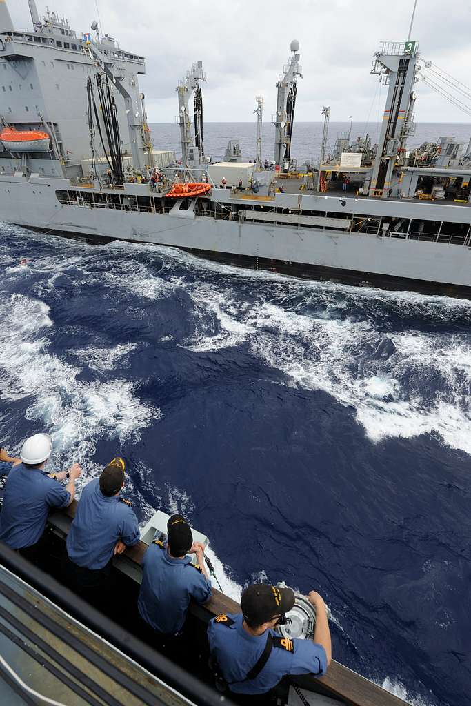 Members of the bridge team, including Cmdr. Angus Topshee, commanding officer of the Canadian navy destroyer HMCS Algonquin, R17), observe a replenishment at sea.