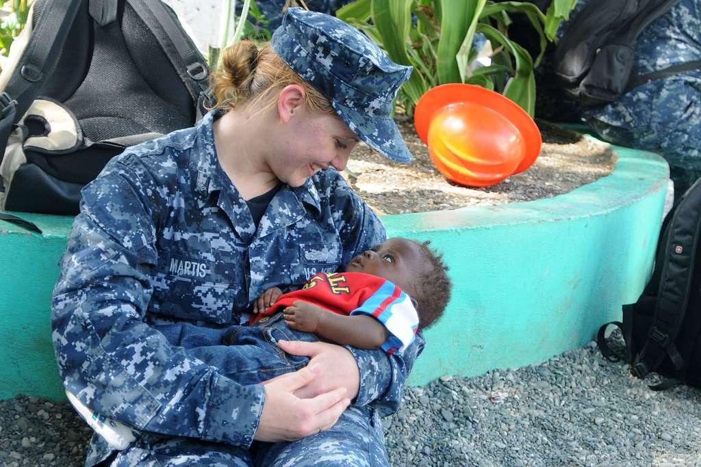 Yeoman 2nd Class Rachel Martis, assigned to the amphibious assault ship USS Iwo Jima (LHD 7), cradles a Haitian child during a community service project