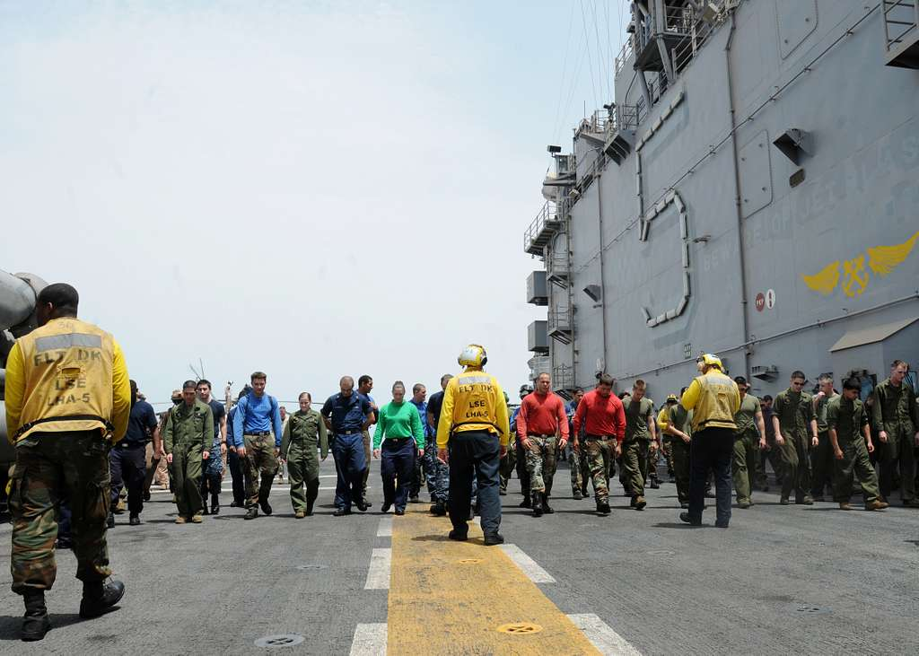 Sailors and Marines conduct a foreign object debris walkdown prior to flight operations aboard the amphibious assault ship USS Peleliu (LHA 5).