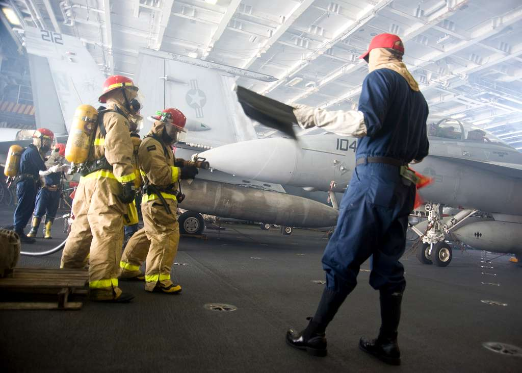 Sailors aboard USS George Washington (CVN 73) combat a simulated fire during a general quarters drill.