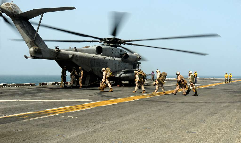 U.S. Marines board a Marine Corps CH-53E Super Stallion helicopter assigned to the White Knights of Helicopter Marine Medium (HMM) 165 aboard the amphibious assault ship USS Peleliu (LHA 5).
