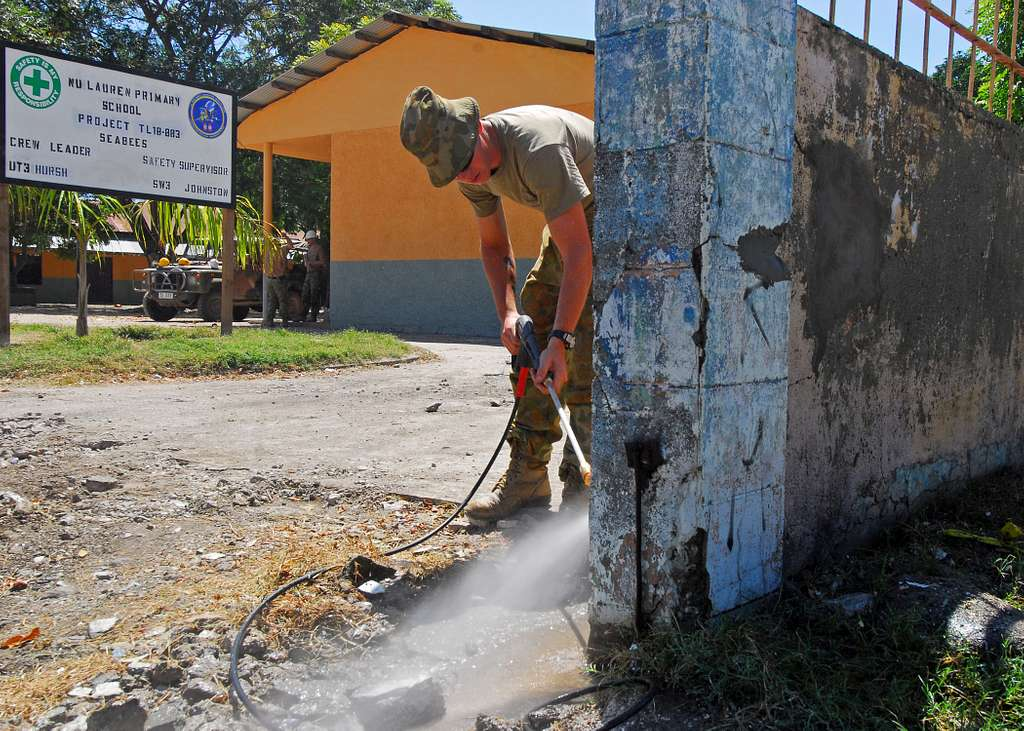 Royal Australian Engineer Sapper David Kober pressure washes a wall before painting during a Pacific Partnership engineering civic action program event at Nu Laran School in Dili,