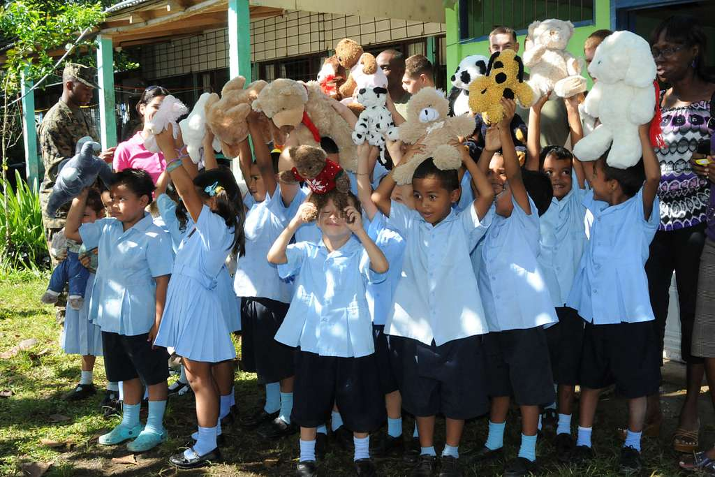 Children from Hone Creek primary school hold up stuffed animals given to them by service members embarked aboard the amphibious assault ship USS Iwo Jima (LHD 7).