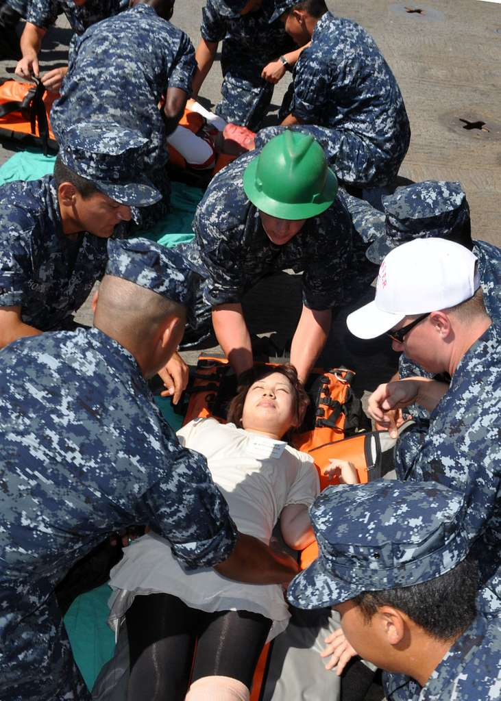 Stretcher-bearers and members of the Medical Training Team prepare to move victims to a safe location during a simulated mass casualty drill aboard the amphibious transport dock ship USS Denver (LPD 9).