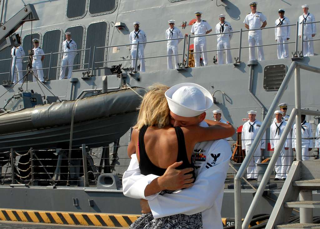 Boatswain's Mate 2nd Class Brandon Carney receives the traditional first kiss from his wife during a homecoming celebration for the guided-missile destroyer USS Cole (DDG 67).