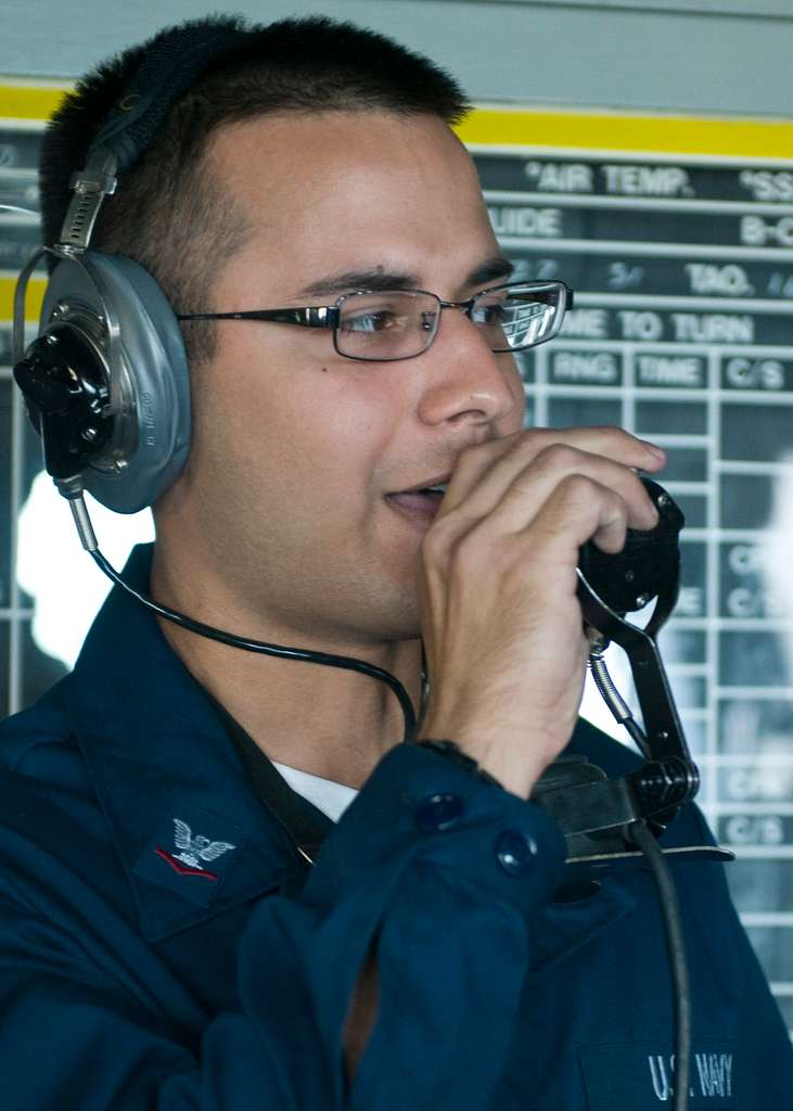 Operations Specialist 3rd Class Rama Aiyer, from Ann Arbor, Mich., relays the ship's bearing to watch standers as the forward-deployed amphibious assault ship USS Essex (LHD 2) gets underway.