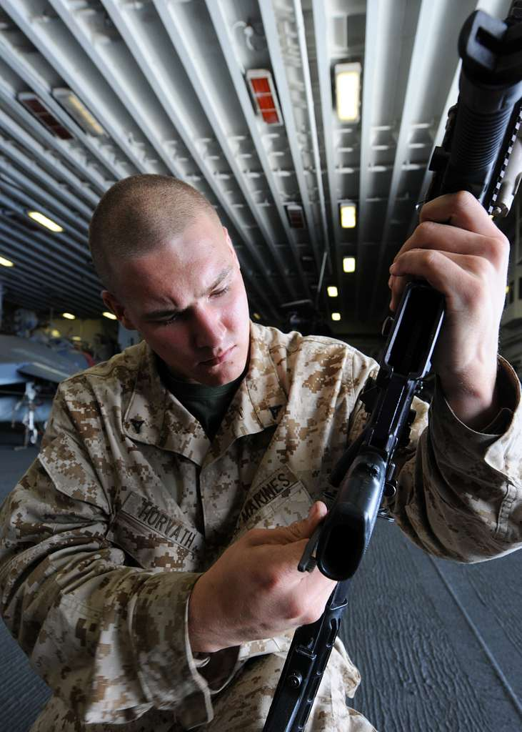 Lance Cpl. Christopher Horvath cleans and inspects his M-16A2 service rifle aboard USS Kearsarge (LHD 3).