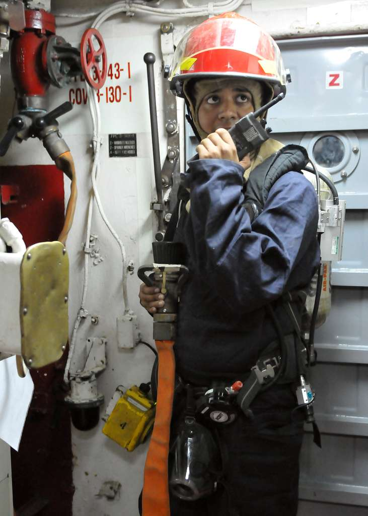 Boatswain's Mate 3rd Class Armando Calvillo, from Nogales, Ariz., relays a message to the repair locker during a total ship survivability exercise aboard the amphibious transport dock ship USS Denver (LPD 9).