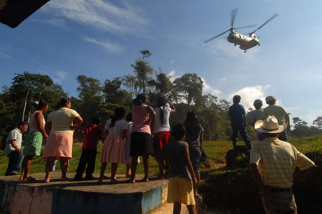 Guatemalan villagers watch as a CH-46E Sea Knight helicopter assigned to the Wild Geese of Marine Medium Helicopter Squadron (HMM) 774 departs their village.