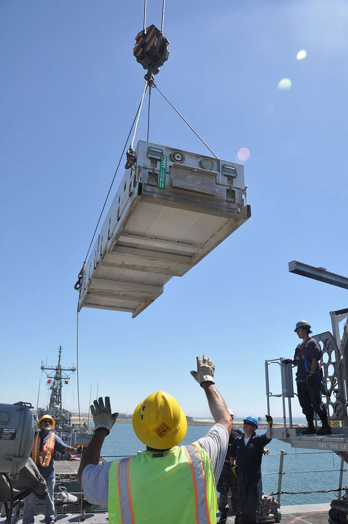 Sailors guide a container onto USS Freedom.