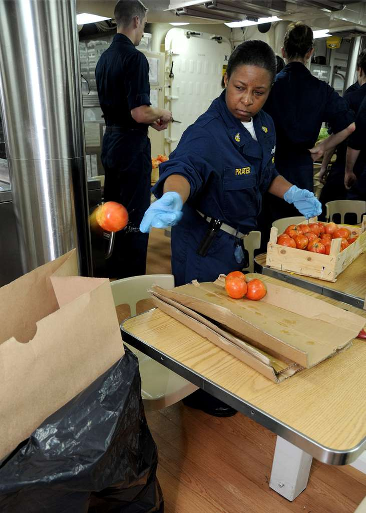 Senior Chief Engineman Selena Prater inspects tomatoes for bacteria and mold during a replenishment at sea aboard the guided-missile destroyer USS Winston S. Churchill (DDG 81).