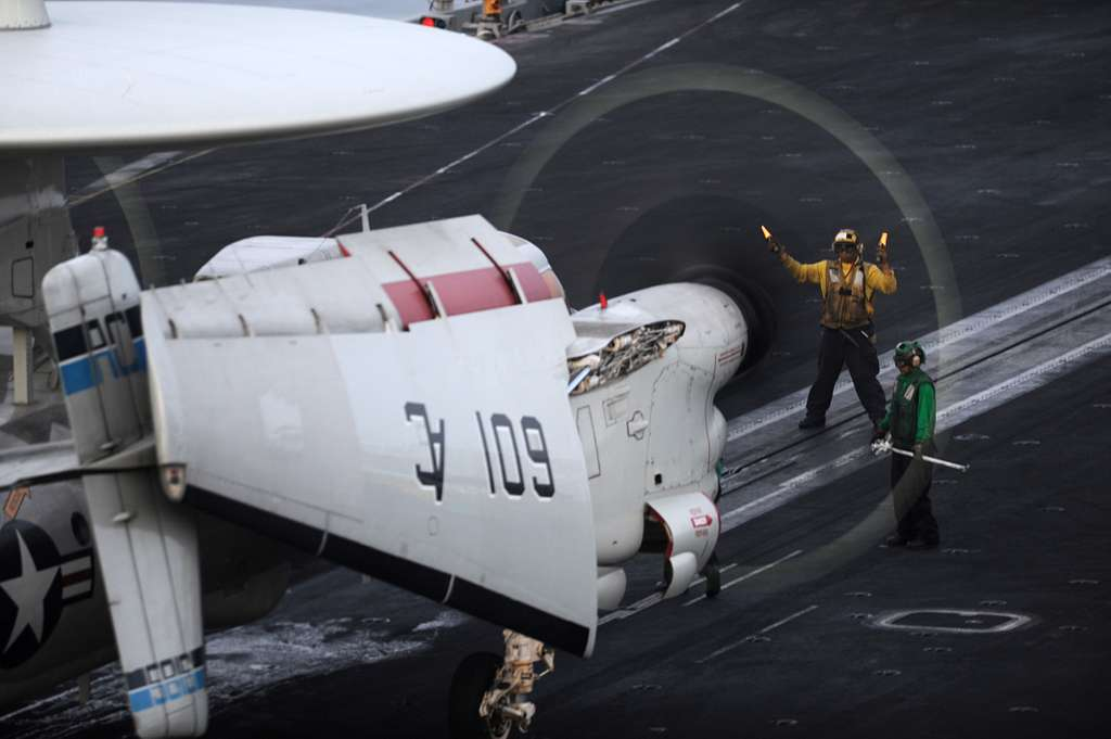 A flight deck plane director lines up an E-2C Hawkeye for launch during night flight operations aboard the aircraft carrier USS Harry S. Truman (CVN 75).