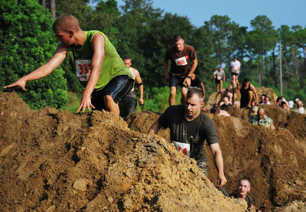 Participants in the 15th Annual Seabee Volkslauf Mud Run make their way over a obstacle in the five-mile course at Naval Construction Battalion Center.