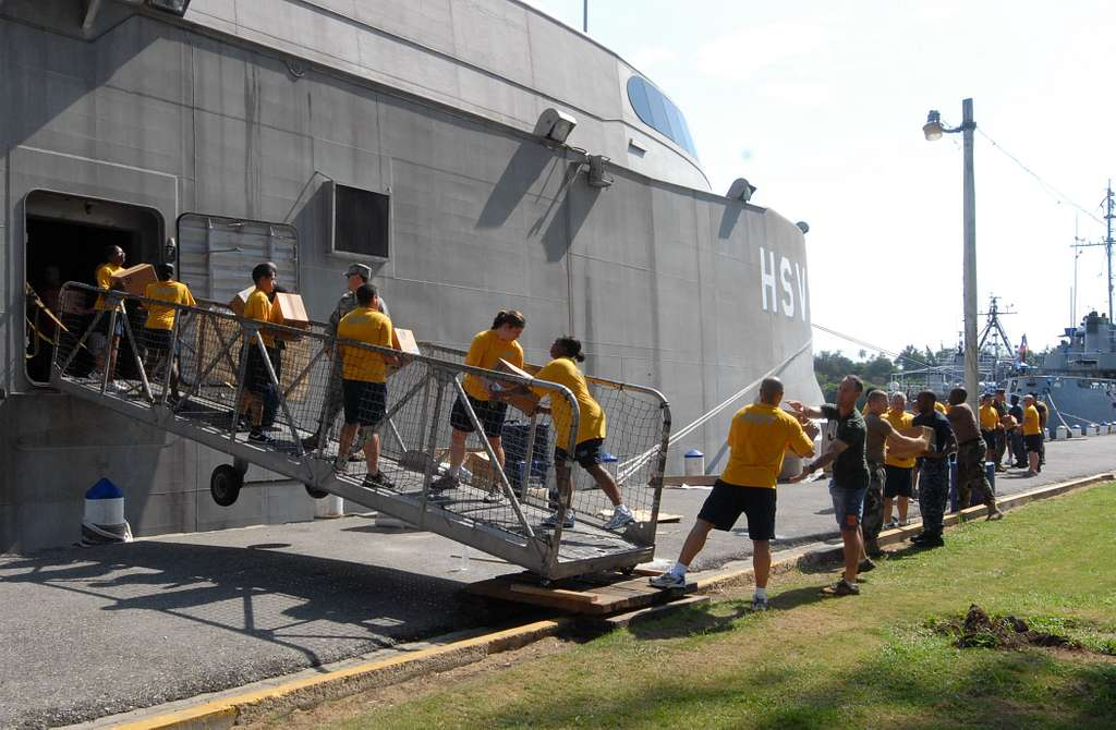 Personnel embarked aboard High Speed Vessel Swift (HSV 2) unload pallets of Project Handclasp aid to be donated to relief organizations.