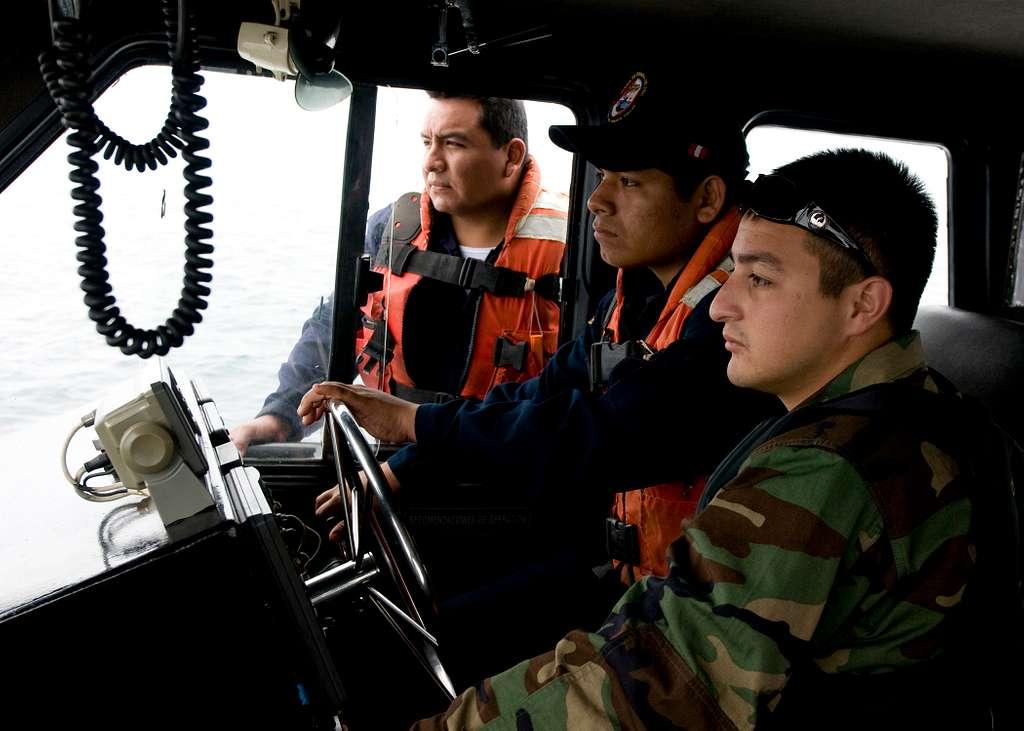 Boatswain's Mate 2nd Class Daniel Mendoza, right, supervises a Peruvian coast guardsman's coxswain skills during coxswain tactical maneuver skills training aboard the Peruvian patrol boat PC 228 Coishco.