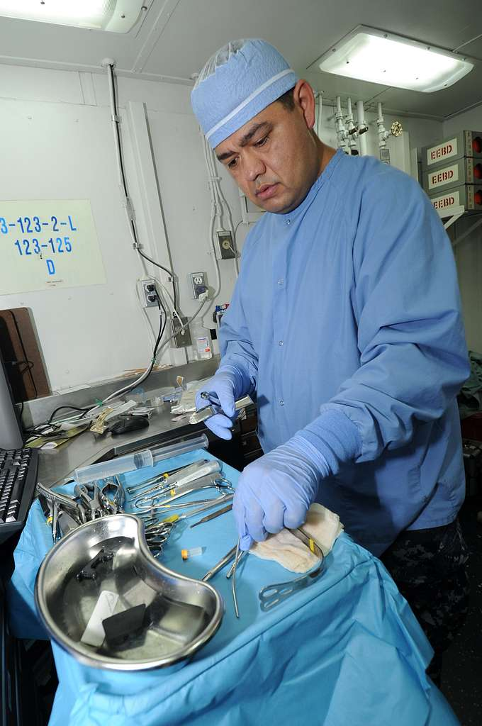 Hospital Corpsman 1st Class Salvador Lopez, from Coachella Valley, Calif., organizes surgical tools before an oral surgery in a dental department operating room aboard the aircraft carrier USS George Washington (CVN 73).